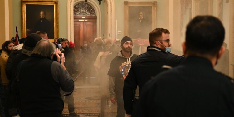 Supporters of US President Donald Trump enter the US Capitol as smoke fills the corridor on January 6, 2021, in Washington, DC. There are no reports of tear gas being used at the Capitol. - Demonstrators breeched security and entered the Capitol as Congress debated the a 2020 presidential election Electoral Vote Certification. (Photo by Saul LOEB / AFP) (Photo by SAUL LOEB/AFP via Getty Images)