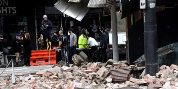 People gather near a damaged building in the popular shopping Chapel Street in Melbourne on September 22, 2021, after a 5.8-magnitude earthquake. (Photo by William WEST / AFP)